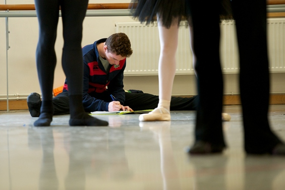 A dance student takes notes during a pas de deux class.